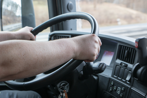 Picture of truck driver with hands on wheel